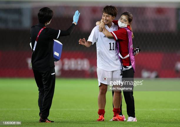 Mina Tanaka of Team Japan celebrates their side's victory with members of staff after the Women's Group E match between Chile and Japan on day four...