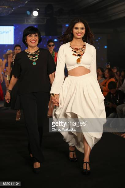 Minakshi Dixit walks the runway with Mona Shroff during India Intimate Fashion Week 2017 at Hotel Leela on March 18 2017 in Mumbai India
