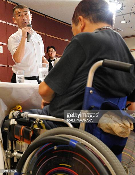 Minamata disease patient Kenji Nagamoto stands beside other patients as he criticizes a bill during a press conference in Tokyo on July 8 2009 The...
