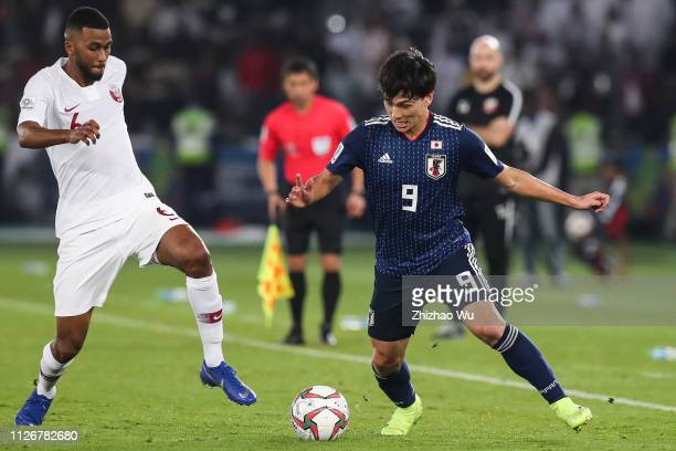 Minamino Takumi of Japan competes with Abdel Aziz Hatim of Qatar during the AFC Asian Cup final match between Japan and Qatar at Zayed Sports City...