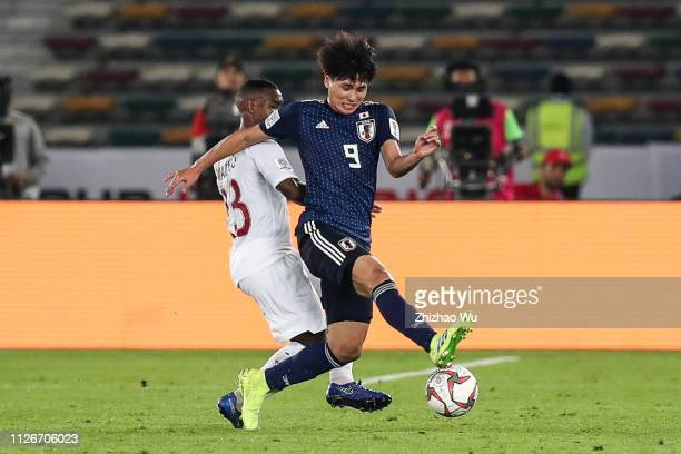 Minamino Takumi of Japan competes with Assim Omer Madibo of Qatar during the AFC Asian Cup final match between Japan and Qatar at Zayed Sports City...