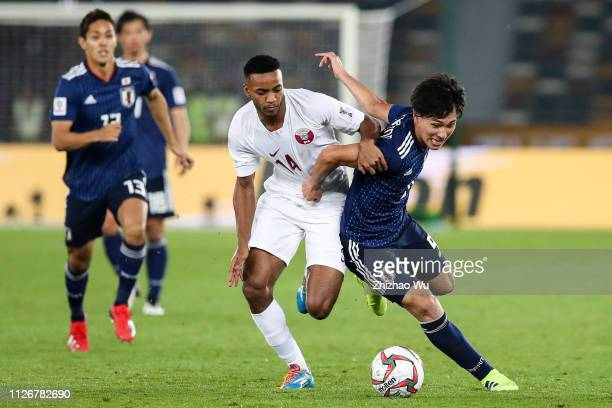 Minamino Takumi of Japan competes with Salem Al Hajri of Qatar during the AFC Asian Cup final match between Japan and Qatar at Zayed Sports City...