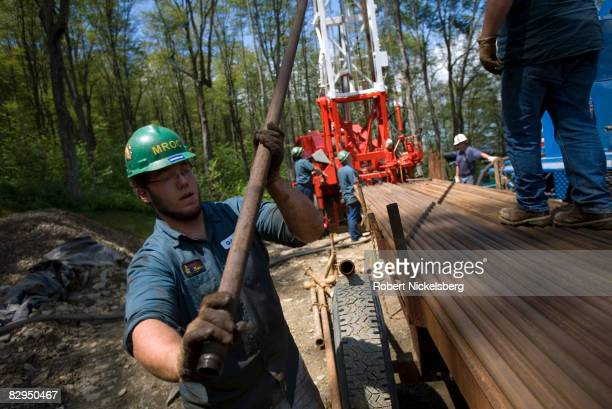 Minard Run Oil Company drilling team removes steel pipe sections from a recently drilled gas well whose side walls were notched before a high...