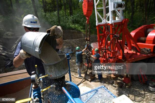 Minard Run Oil Company drilling team waits for sand to be pumped into steel pipe sections lowered into a recently drilled 2100 foot gas well to...