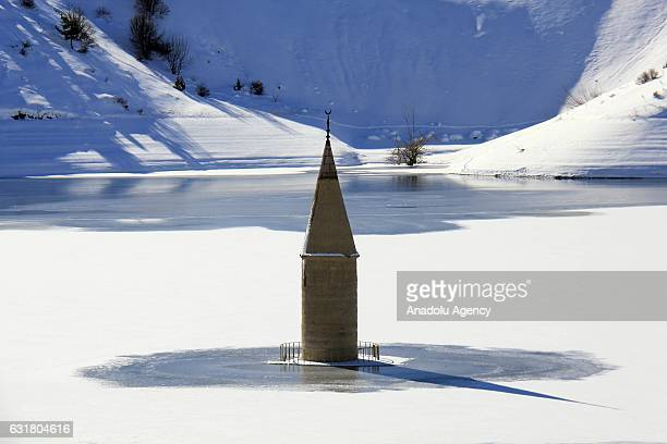 Minaret of a mosque is seen on the surface of PusatOzen dam lake in Sivas Turkey on January 16 2017 Dropping water levels resulting from frost reveal...