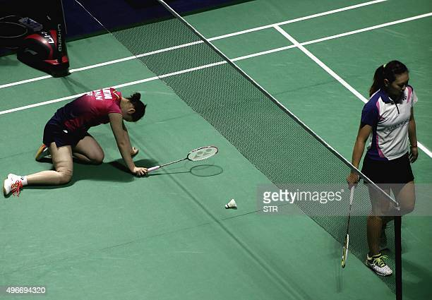 Minatsu Mitani of Japan falls on the court during the women's singles first round match against Zhang Beiwen of the US at the China Open badminton...