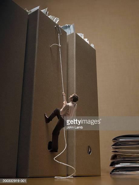 Minature businessman climbing giant folder (digital composite)