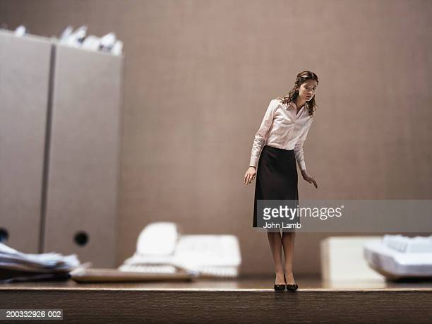 Minature businesswoman standing on edge of desk (digital composite)