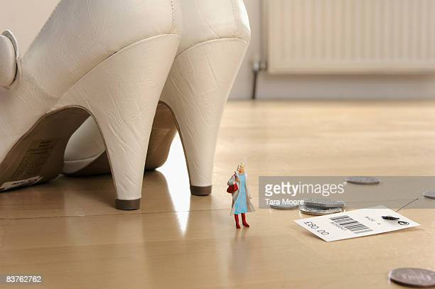 minature woman standing beside shoes,money and tag