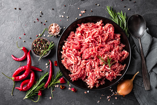 Mince. Ground meat with ingredients for cooking on black background. Top view 907849968