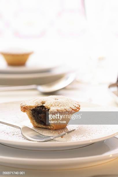 Mince pie on plate with bite taken out, close up