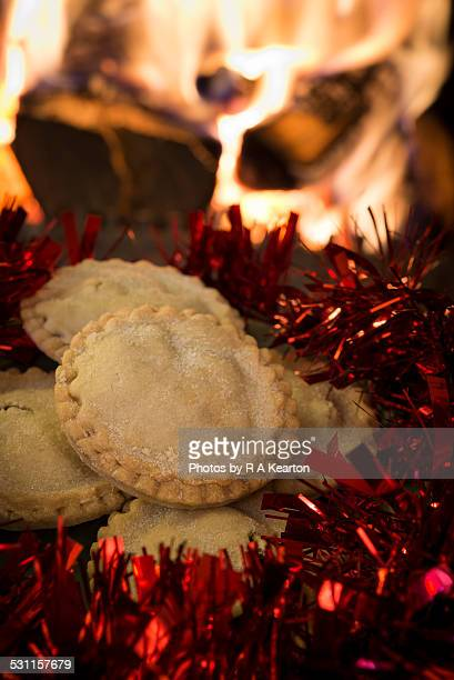 Mince pies and red tinsel before a log fire