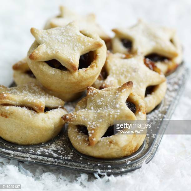 Mince pies dusted with icing sugar in the baking tin