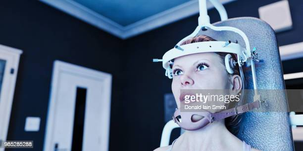 mind control: woman strapped in chair undergoing therapy - female torture stock-fotos und bilder