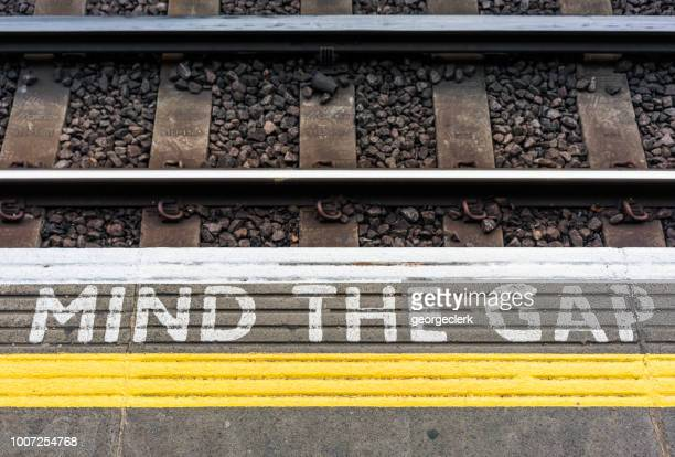 mind the gap sign on a london underground station platform - separation stock photos and pictures
