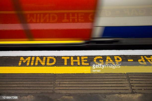 mind the gap sign on london underground - metropolitana di londra foto e immagini stock