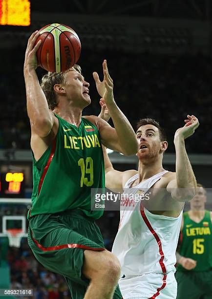 Mindaugas Kuzminskas of Lithuania looks to shoot against Victor Claver of Spain during the Men's Preliminary Round Group B between Spain and...