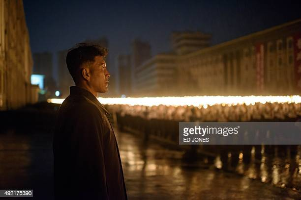 A minder watches a torchlighting performance at Kim IlSung square in Pyongyang on October 10 2015 North Korea was marking the 70th anniversary of its...