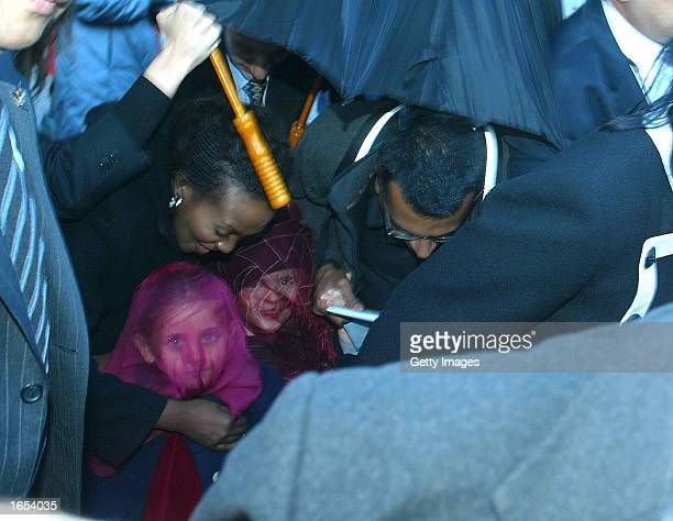 Minders escort the veiled children of Michael Jackson as they visit the Berlin zoo November 20 2002 in Berlin Germany Jackson took his children to...