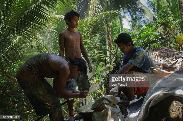 Minders gather around a hose in the mountainside camp to wash their faces during a short break from the tunnels on April 22 2014 in PinutAn...