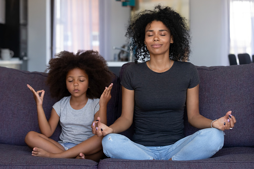 Mindful african mom with funny kid daughter doing yoga together 1126384516