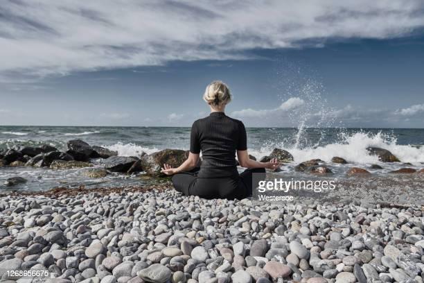 mindful vrouw op strand - er even tussenuit stockfoto's en -beelden