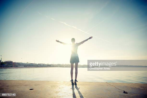 Mindful Young Woman Salutes Rising Sun at Ocean