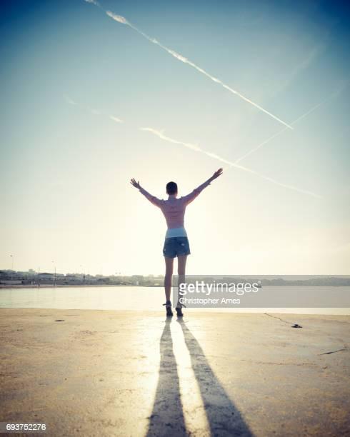 Mindful Young Woman Salutes Rising Sun at Ocean