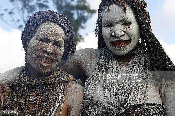 Mindima widows wearing numerous strings of seeds known as 'Job's tears' huddle together near a camp fire before the 46th annual singsing in the...