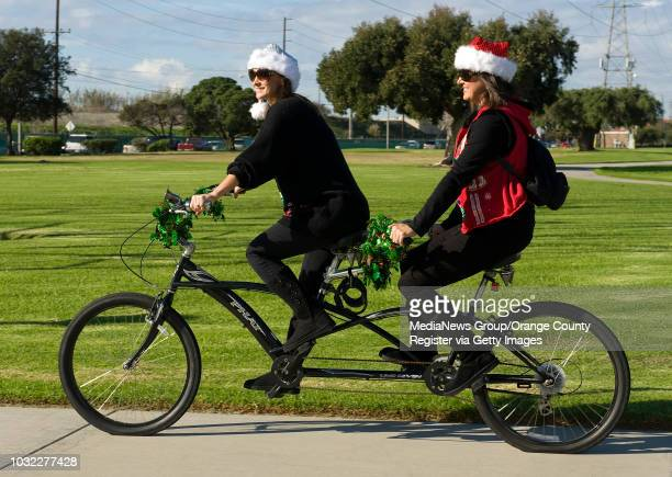Mindy Coppolino left and Lori DeStefano ride their bicycle built for two in the 2nd Annual Ugly Christmas Sweater Bike Ride in Huntington Beach...