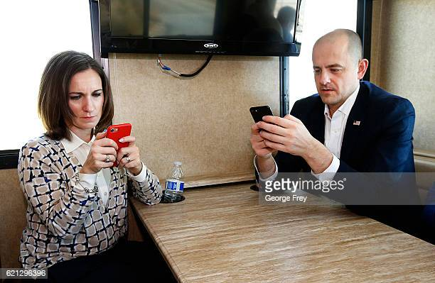 Mindy Finn running mate of US independent presidential candidate Evan McMullin look at their phones as they ride in an RV between events on November...