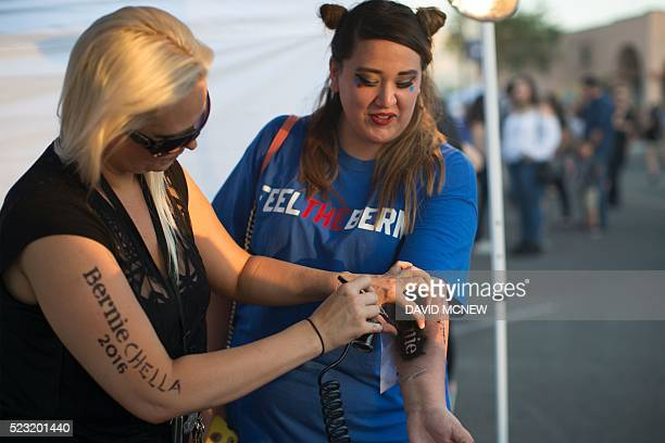 Mindy Harris gives a Bernie Sanders supporter an airbrushed temporary Sanders tattoo during a twoday free concert event dubbed Berniechella in...