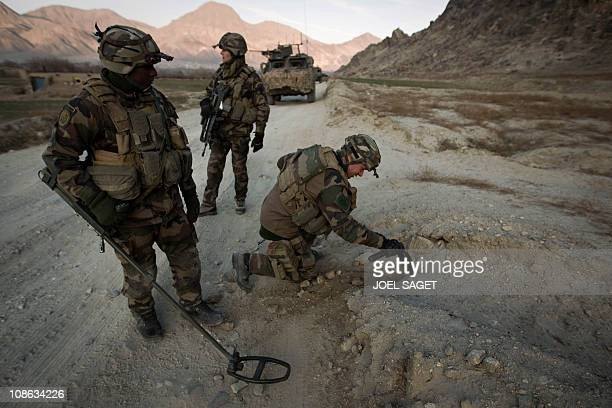 Mine clearing specialists from the French Foreign Legion 1st section 'Les Aigles ' of the 2nd REG search for improvised explosive devices on a road...
