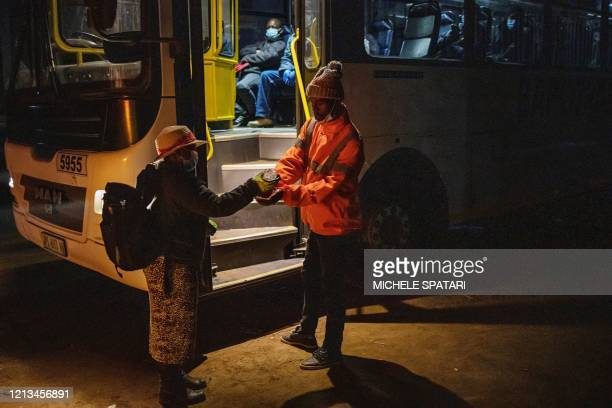 A mine employee sanitises the hands of a mine worker en route to his evening shift at the SibanyeStillwater platinum mine before boarding a company...
