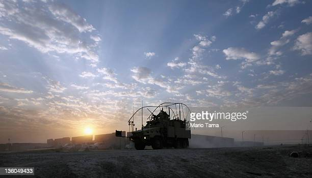 Mine Resistant Ambush Protected vehicle drives past blast walls through the nearly deserted Camp Adder, now known as Imam Ali Base, on December 16,...