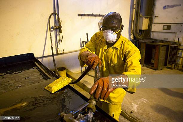 A mine worker cleans a large ingot of gold on a workbench during the refining process at the production plant for the LouloGounkoto gold mine complex...