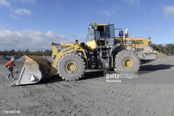 Mine worker clears debris near a Komatsu Ltd. WA500 front loader at a run-of-mine pad of the Kirkland Lake Gold Ltd. Fosterville Gold Mine in...