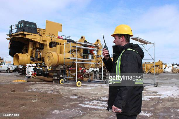 A mine worker directs a giant excavator at the ArcelorMittal mining complex March 21 2012 in Fermont Quebec Canada one of North America's leading...