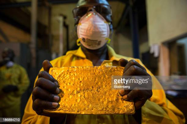 A mine worker displays a large ingot of gold after cleaning and hammering it during the refining process at the production plant for the...