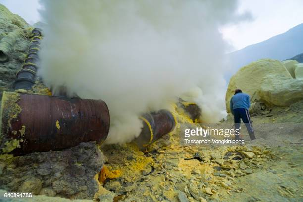 mine worker extracting solid sulfur at kawah ijen volcano crater - sulfuric acid stock photos and pictures