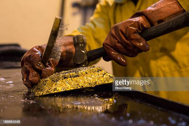 A mine worker hammers a large ingot of gold after removing it from its mould during the refining process at the production plant for the...