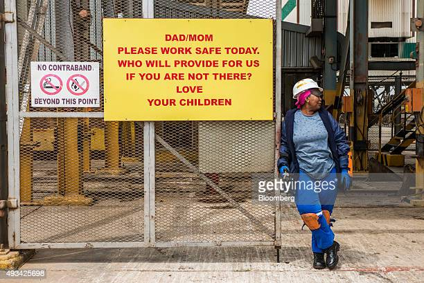 Mine worker stands beside a safety sign at the entrance to the shaft at Harmony Gold Mining Co.'s Doornkop mine west of Johannesburg, South Africa,...
