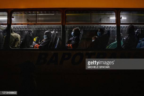 Mine workers en route to their evening shift at the SibanyeStillwater platinum mine wait on board of a company bus at the Wonderkop taxi rank in...
