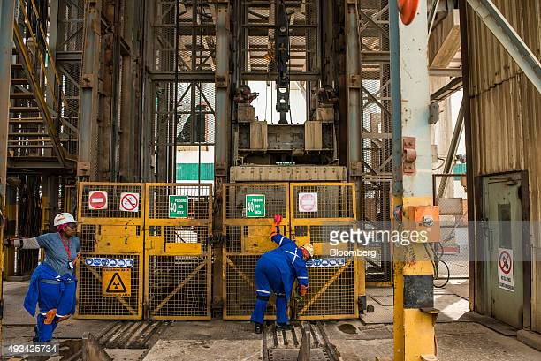 Mine workers secure elevator safety gates at the entrance to the mine shaft at Harmony Gold Mining Co's Doornkop mine west of Johannesburg South...