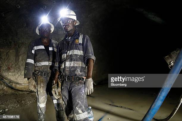 Mine workers watch as colleagues drill a nearby rock wall in the underground tunnels at the Kibali gold mine operated by Randgold Resources Ltd in...
