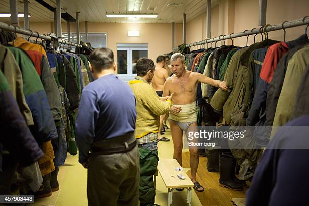 Mine workers wrap themselves in warm clothes to protect themselves from cold in the changing room before going underground at the OAO Alrosa diamond...