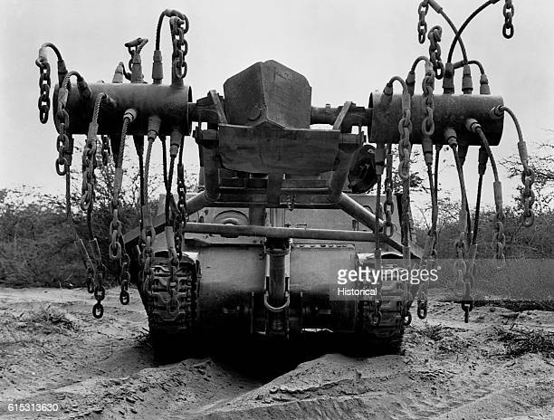A minedetonator installed on a Marine M4 tank by Seabees uses chaintipped flails mounted on tubular hubs which whirl around to detonate contact mines...