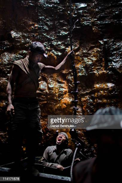Miner calls to the crane operator, sitting 300 feet above, to hoist them out of a coal mine for their lunch break on April 13, 2011 near the village...