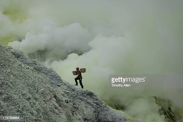 Miner carriers sulfur blocks up volcanic cliff