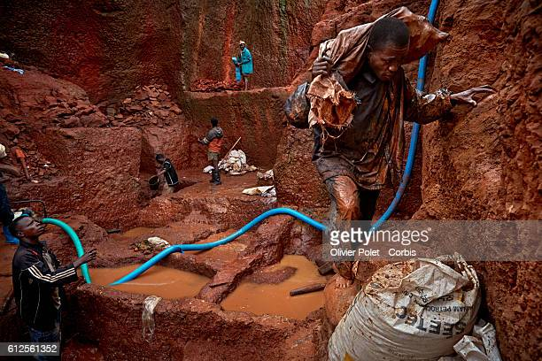 Miner carries a bag filled with excess earth out of his concession as colleagues pump out rain water and break up chunks of diamondrich rock layers...